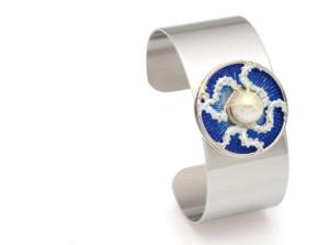 Een stalen armband met daarop een blauw emaille schijf, een opengewerkte 'octopus' in zilver en emaille en een zoetwater parels